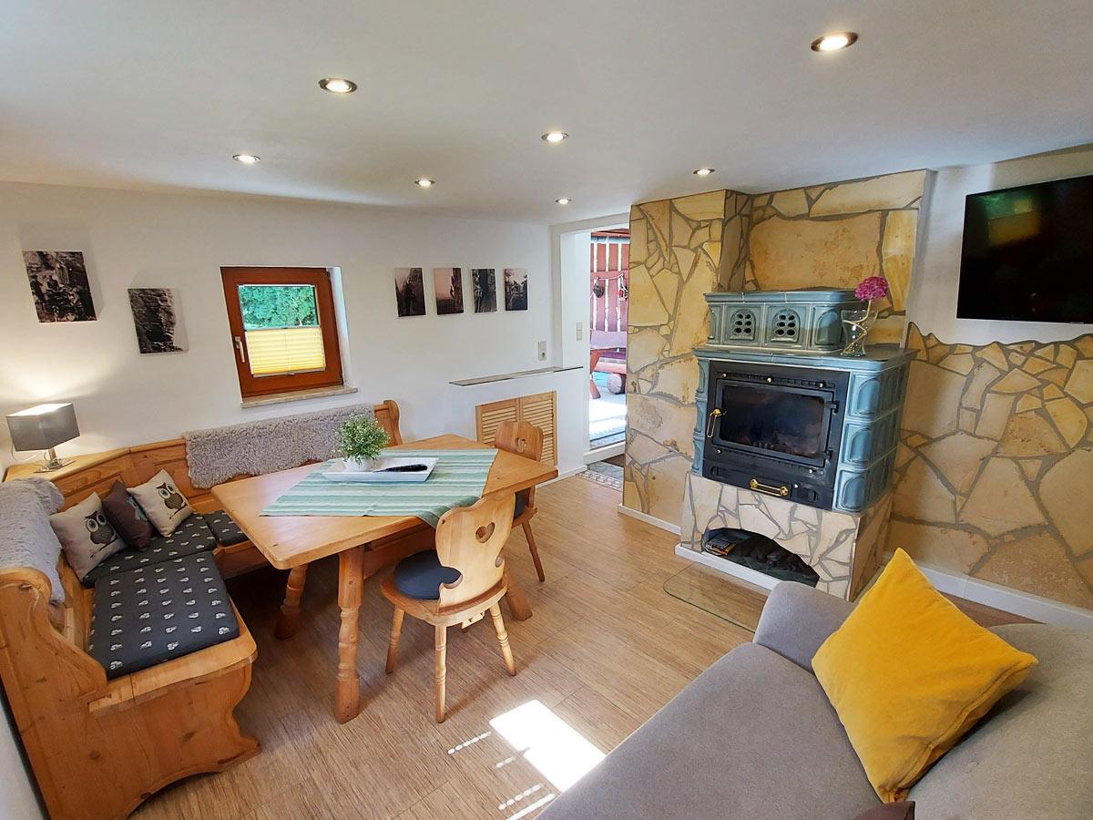Ferienhaus Bergsteigerhütte - Wohnzimmer mit Sofa Essecke und Kamin