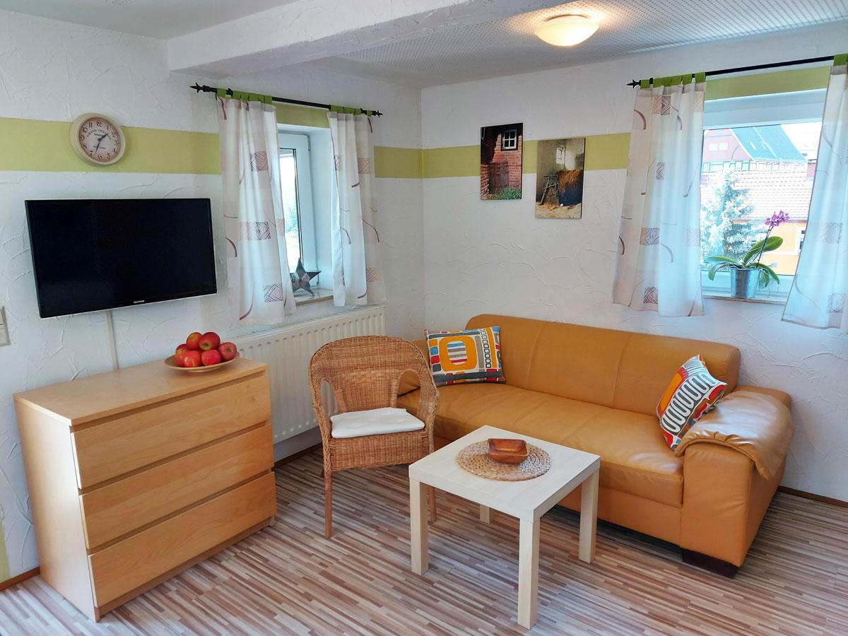 Ferienhaus Schrammsteinblick - Ferienwohnung1 - Wohnzimmer mit TV und Sofa
