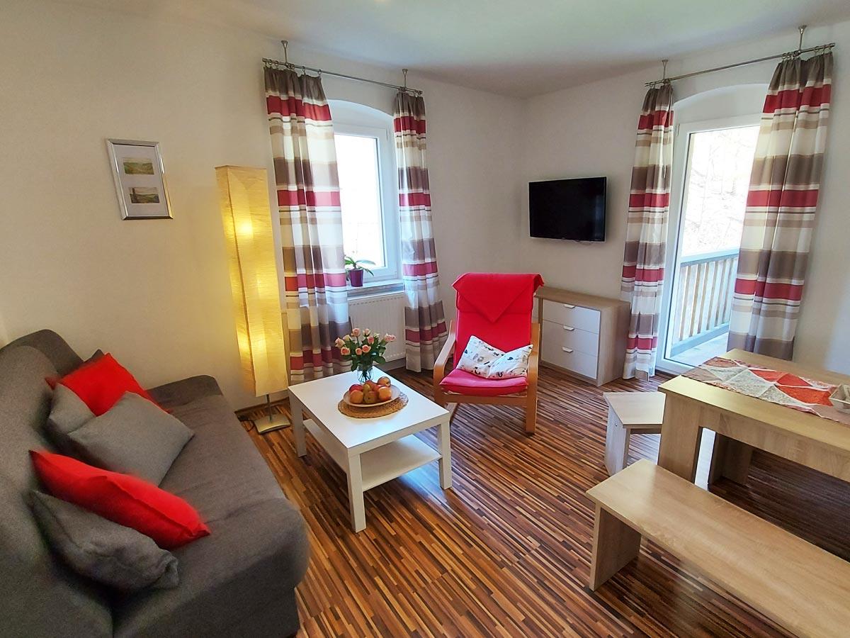 Ferienhaus Zum Kirnitzschtal - Ferienwohnung1 - Wohnzimmer mit Sofa und TV